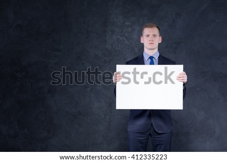 Shot of a young blonde man holding a big blank paper