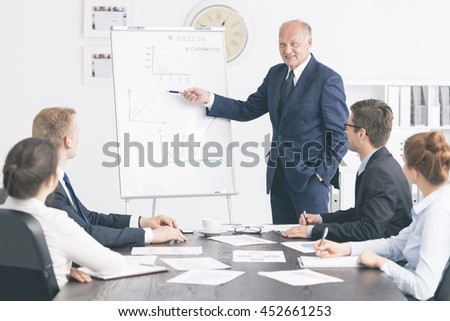 Shot of an elegant senior boss giving an oveview to employees