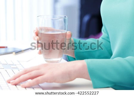 Shot of an professional woman holding in her hand a glass of water while sitting at office in front of computer and typing on keyboard.