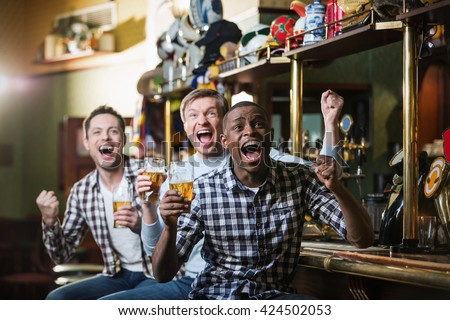 Shouting fans with a beer at a bar