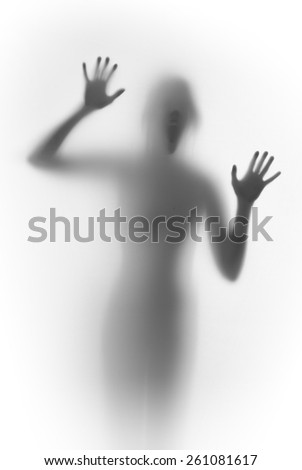Shouting scary face and body silhouette behind a glass surface