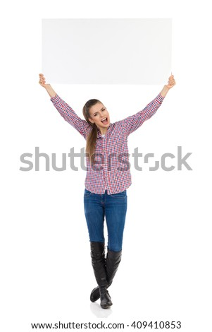 Shouting young woman in jeans, black boots and lumberjack shirt standing and holding white placard above her head. Full length studio shot isolated on white.