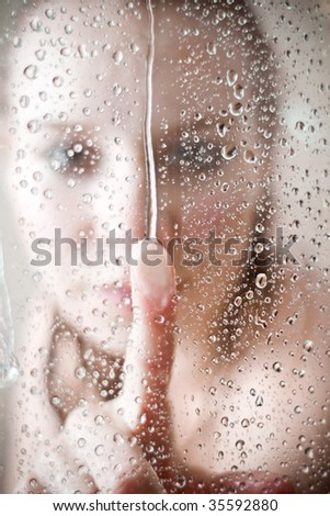 showering woman shot from behind glass