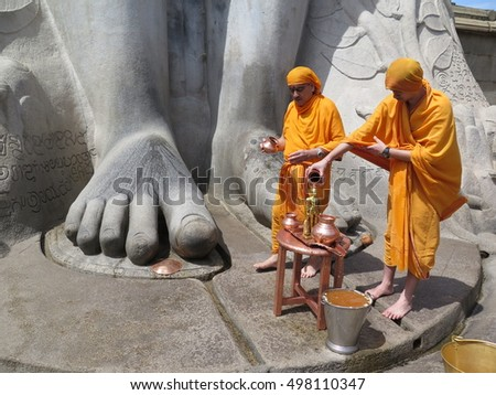 SHRAVANABELAGOLA (INDIA) 26TH JULY 2015: Buddhist monks blessing their gods in a celebretion day. The monks are bathing the god.
