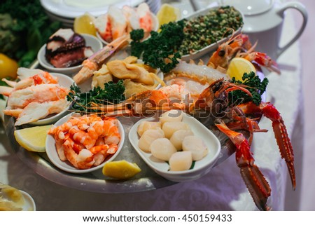 Shrimps and salted fish stand on the plate with lobsters