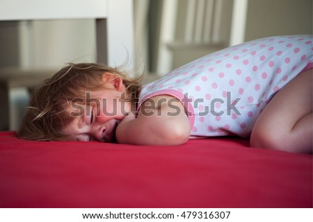 Sick baby girl lying in bed with a fever, crying
