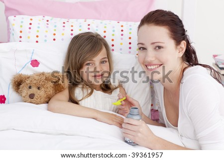 Sick little girl in bed taking cough medicine with her mother