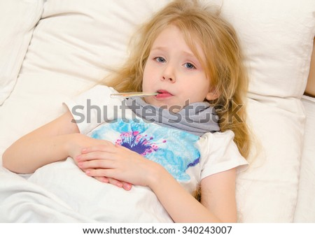 Sick little girl lying in the bed with thermometer in her mouth