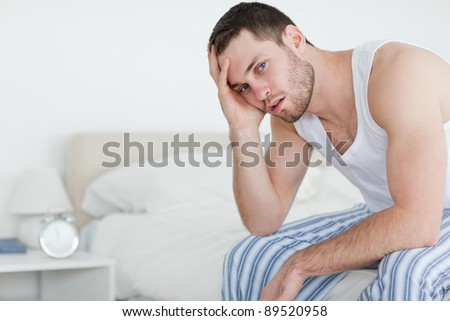 Sick man sitting on his bed while looking at the camera
