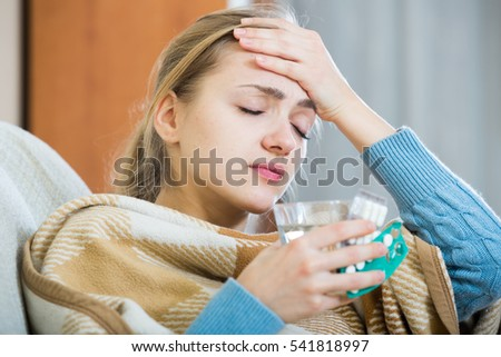 Sick young woman under blanket in domestic interior