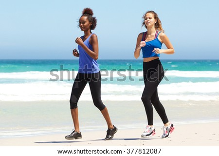 Side portrait of two young women running by water on beach
