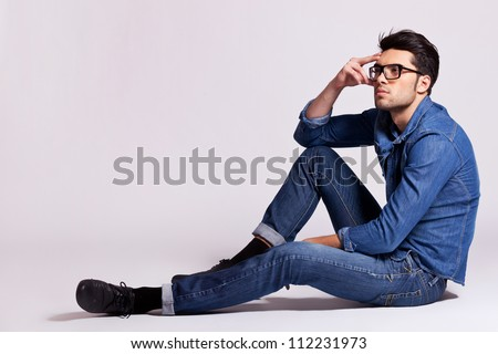 Side View Of A Casual Fashion Man Sitting On Gray Background And Looking Away From The