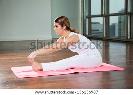 Side view of a young woman practicing yoga called Seated Forward Bend in gym
