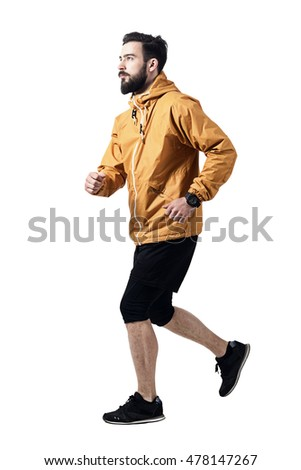 Side view of athletic man jogging in jacket looking up. Toned desaturated full body length portrait isolated on white studio background.