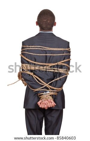 Side view of businessman executive tied up with rope, looking up standing back