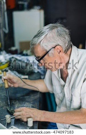 side view of elderly man in glasses working with electric object at table in workshop