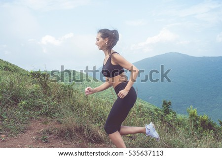 Side view of female athlete training, running outdoors in green mountains. Young woman wearing black sportswear working out  in summer