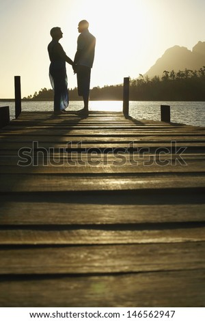 Side view of happy senior couple standing on edge of pier by lake at sunset