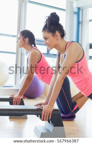 Side view of two fit women performing step aerobics exercise in gym