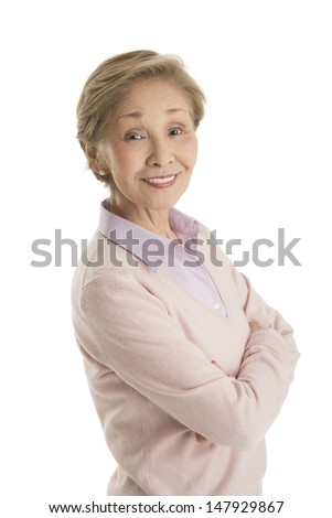 Side view portrait of senior businesswoman standing arms crossed against white background