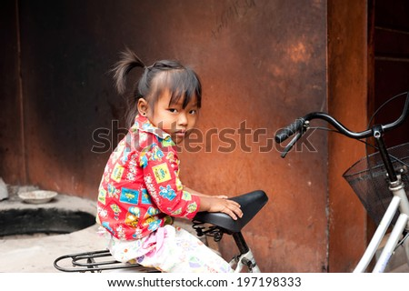 SIEM REAP, CAMBODIA - DEC 22, 2013: Unidentified khmer cute little girl in colorful clothes sitting on  bicycle at street over grunge wall background on Dec 22, 2013 in Siem Reap, Cambodia