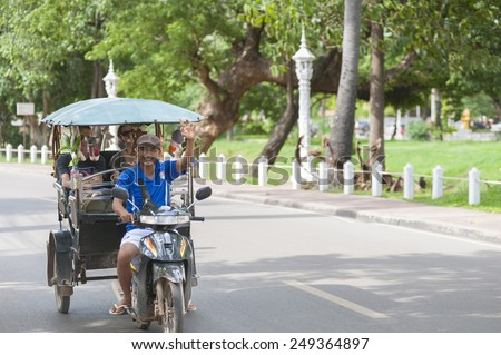 SIEM REAP, CAMBODIA - JUNE 28, 2014: An unidentified tuktuk driver drives Caucasian tourists in the street. The town is famous for its proximity to Angkor temples and night markets.