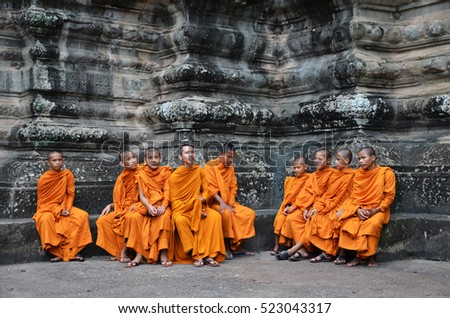 SIEM REAP, CAMBODIA - OCT 20, 2016: Buddhist monk in reddish yellow robes in one of the famous temples of Angkor Wat, Siem Reap, Cambodia