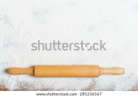 Sifted flour and rolling pin on the table. Kitchen background