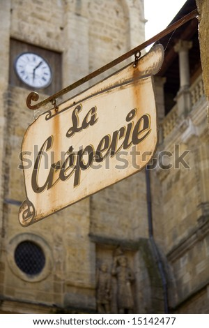 Sign for a French Creperie in front of a church clock