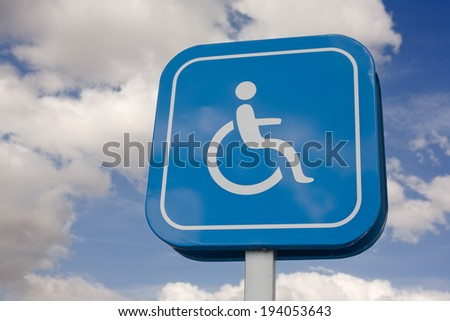 Signal that indicate priority parking for vehicles of people with disabilities. Isolated over blue sky with clouds