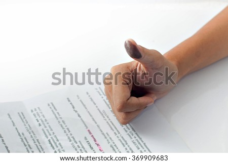 Signing a contract with a thumb print: Image contains thumb with ink stain and blurry typed paper.