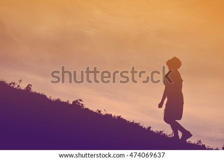 Silhouette a boy walking on sunset