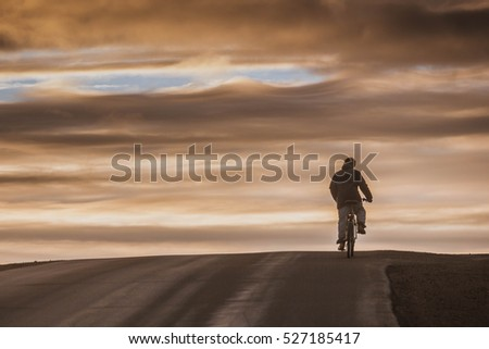 silhouette boy with bike on road red orange sky clouds sunset at the sea with mountain horizon
