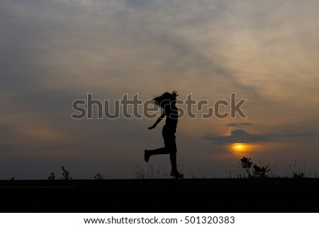 Silhouette girls on holiday. she is happy to be running and jumping at sunset