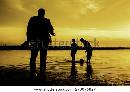 silhouette group of children playing with ball on beach during sunrise, sunset with photographer