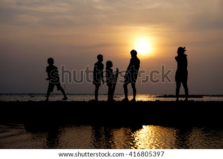 Silhouette group of people at sunset on the beach