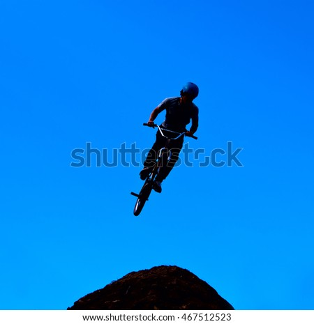 Silhouette image of a cyclist on the background of the sky