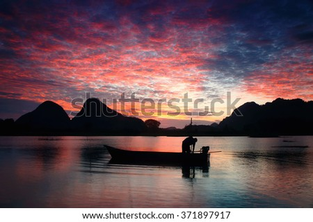 Silhouette local fisherman during sunrise near Timah Tasoh Lake ,Perlis
