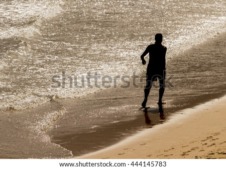 Silhouette Man walking along the beach shore dela