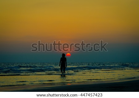 Silhouette man walking on the beach on sunset time
