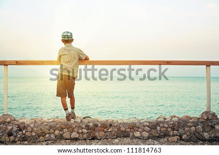 silhouette of a boy standing on quay in the evening during sunset looking at sea
