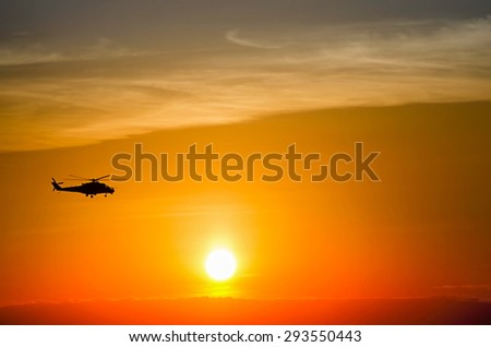 silhouette of a flying helicopter at sunset