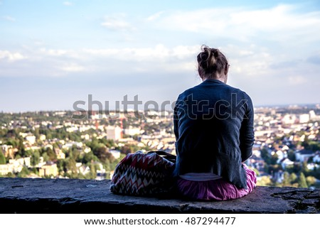 silhouette of a lonely girl sitting on the edge of the parapet of a belvedere
