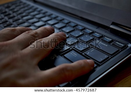 Silhouette of a male finger pressing black key with a caption Enter on the laptop keyboard