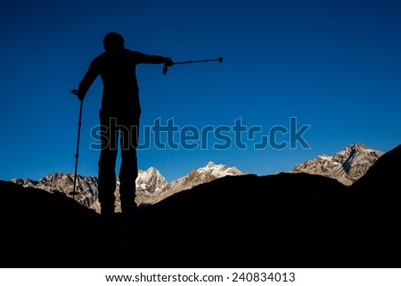 Silhouette of a man pointing with trekking pole towards mountain summit