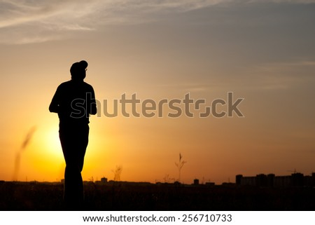 Silhouette of a man walking at the sunset