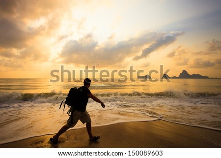 silhouette of a man with a backpack at sunrise on the sea