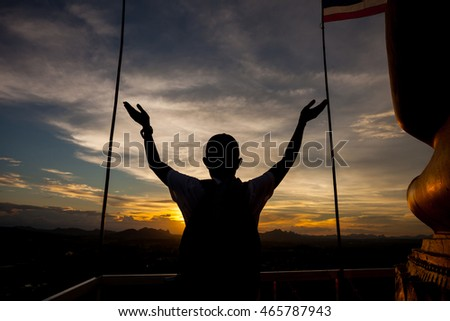 Silhouette of a man with hands raised. sunset