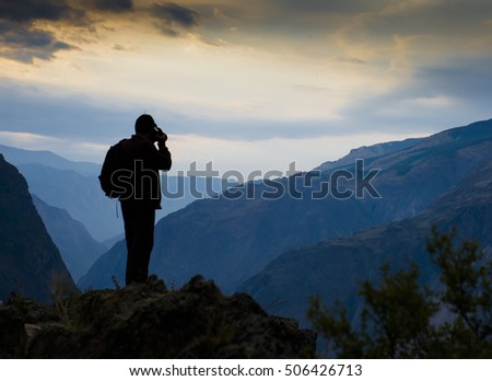 silhouette of a mountain photographer with a backpack