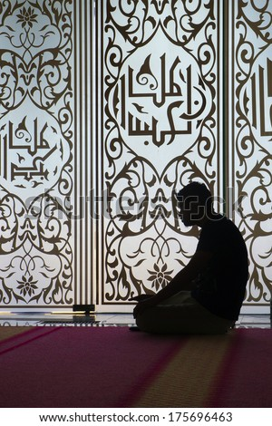 Silhouette of a Muslim praying inside mosque